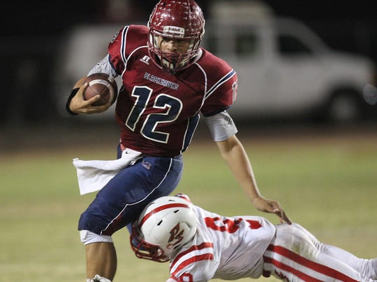 La Quinta quarterback Michael Avina is tackled by Palm Springs' Franklin Miller during a back-and-forth classic on Oct. 17.