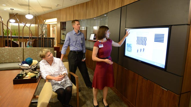 Volunteer Marg Jones (left) watches as Dr. Eric Laro, chairman of the Salem Cancer Institute cancer committee, and Andi Petrone, a business administrator at Salem Hospital, offer a tour of the newly renovated Salem Cancer Institute on Tuesday, Sept. 16, 2014.