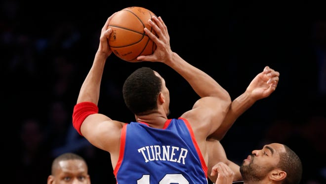 Brooklyn Nets forward Alan Anderson (6) defends Philadelphia 76ers forward Evan Turner (12) as 76ers forward Lavoy Allen (50) looks on from the floor in their NBA basketball game at the Barclays Center, Monday, Feb. 3, 2014 in New York. (AP Photo/Kathy Willens)