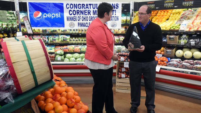 Joe Janes, President and CEO of The Janes Group, right, accepts the Ohio Grocers Association's Pinnacle Award for overall excellence in grocery retail operations from Kristin Mullins, president and CEO of the association, Tuesday at Corner Market.