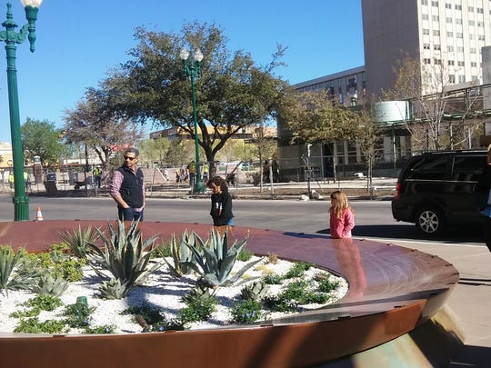 From left, Sergio Rico and his daughters, Frida and Georgia, stop to play Thursday across the street from San Jacinto Plaza. They also looked at the progress of the plaza renovations.