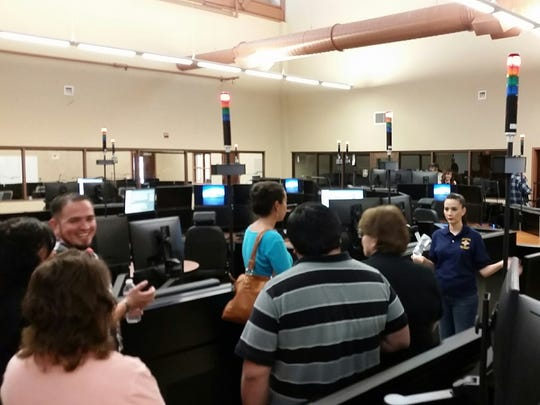 Raquel Grijalva, right, training specialist at the Mesilla Valley Regional Dispatch Authority, shows ribbon-cutting attendees the dispatch floor of a new city-county 911 call center during a tour March 4.