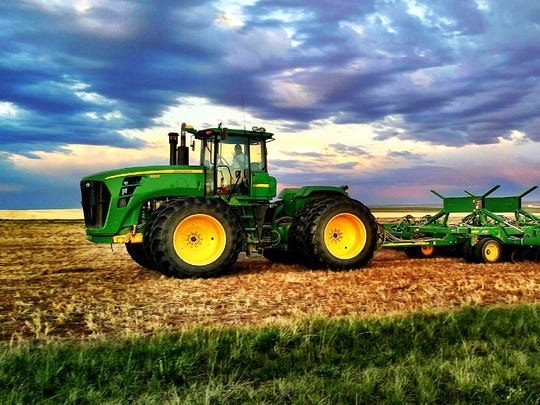 A tractor is parked toward the end of seeding between