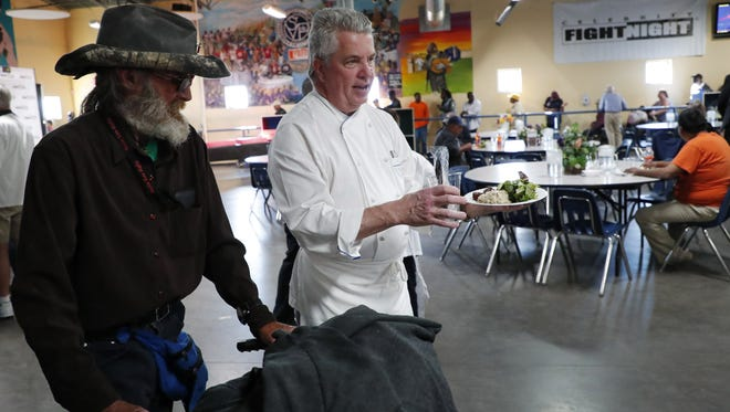 Chef Vincent Guerithault leads a man to a table after preparing meals for the homeless at St. Vincent de Paul in Phoenix on March 6, 2018.