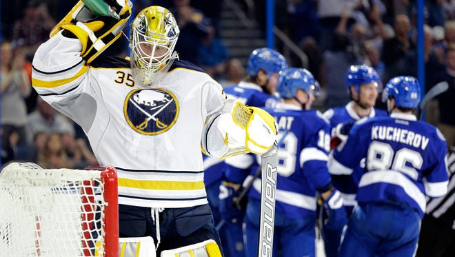 Buffalo Sabres goalie Anders Lindback (35), of Sweden, sprays himself with water as the Tampa Bay Lightning celebrate a goal by Victor Hedman during the second period of an NHL hockey game Tuesday in Tampa, Fla.