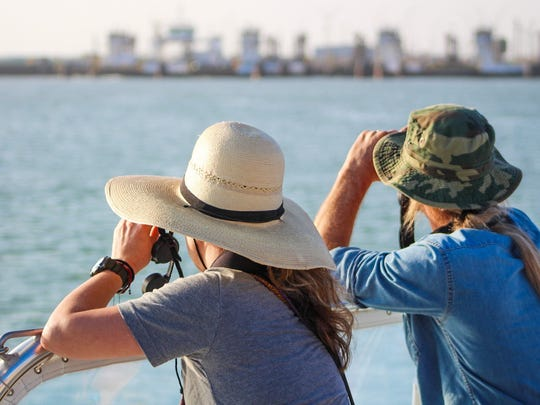Visitors use binoculars to keep an eye out for birds during a nature tour on The Scarlet Lady boat in Port Aransas on Friday, Feb. 23.