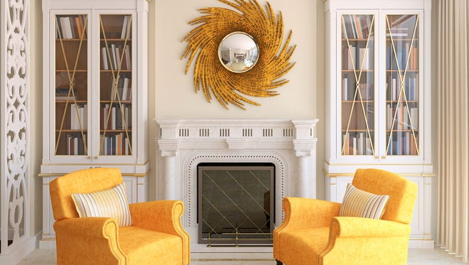 Gold is the primary color in this sophisticated room, highlighted by a swirling gold mirror and a pair of golden-yellow club chairs.