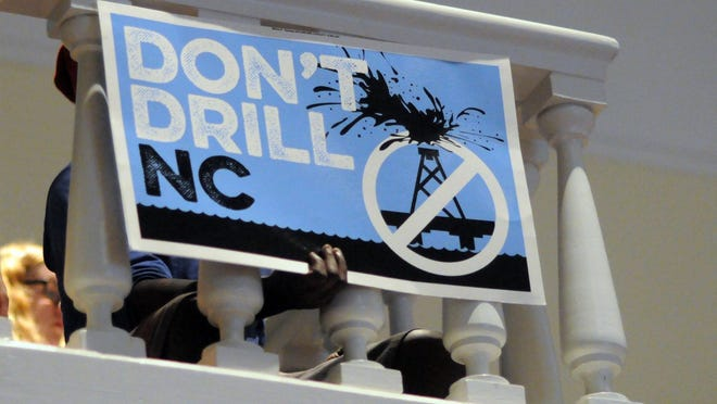 Crowds hold signs opposing offshore drilling at Wilmington City Hall on Tuesday night (July 21, 2015) in Wilmington. Wilmington City Council voted on a resolution to oppose offshore drilling and seismic testing.