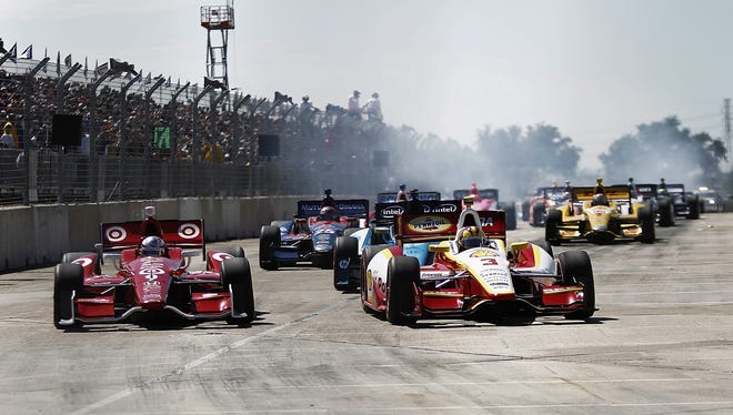 Team Penske's Helio Castroneves, front right, and Target Chip Ganassi Racing's Scott Dixon, front left, lead a pack of cars during the Grand Prix Of Houston Race on Oct. 6.