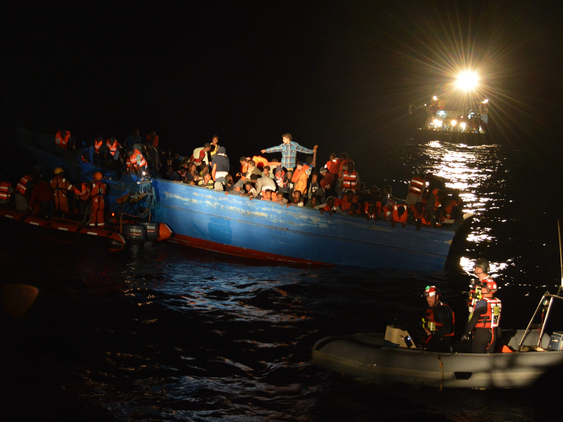 Rescuers work to evacuate 430 refugees who crammed