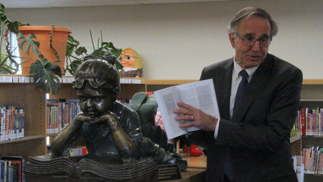 Millicent Petrov Shyne's son, Michael, points to a passage in his mother's book during Saturday's dedication of statue in her memory at the Alamogordo Public Library's Children's Library, 920 Oregon Ave.