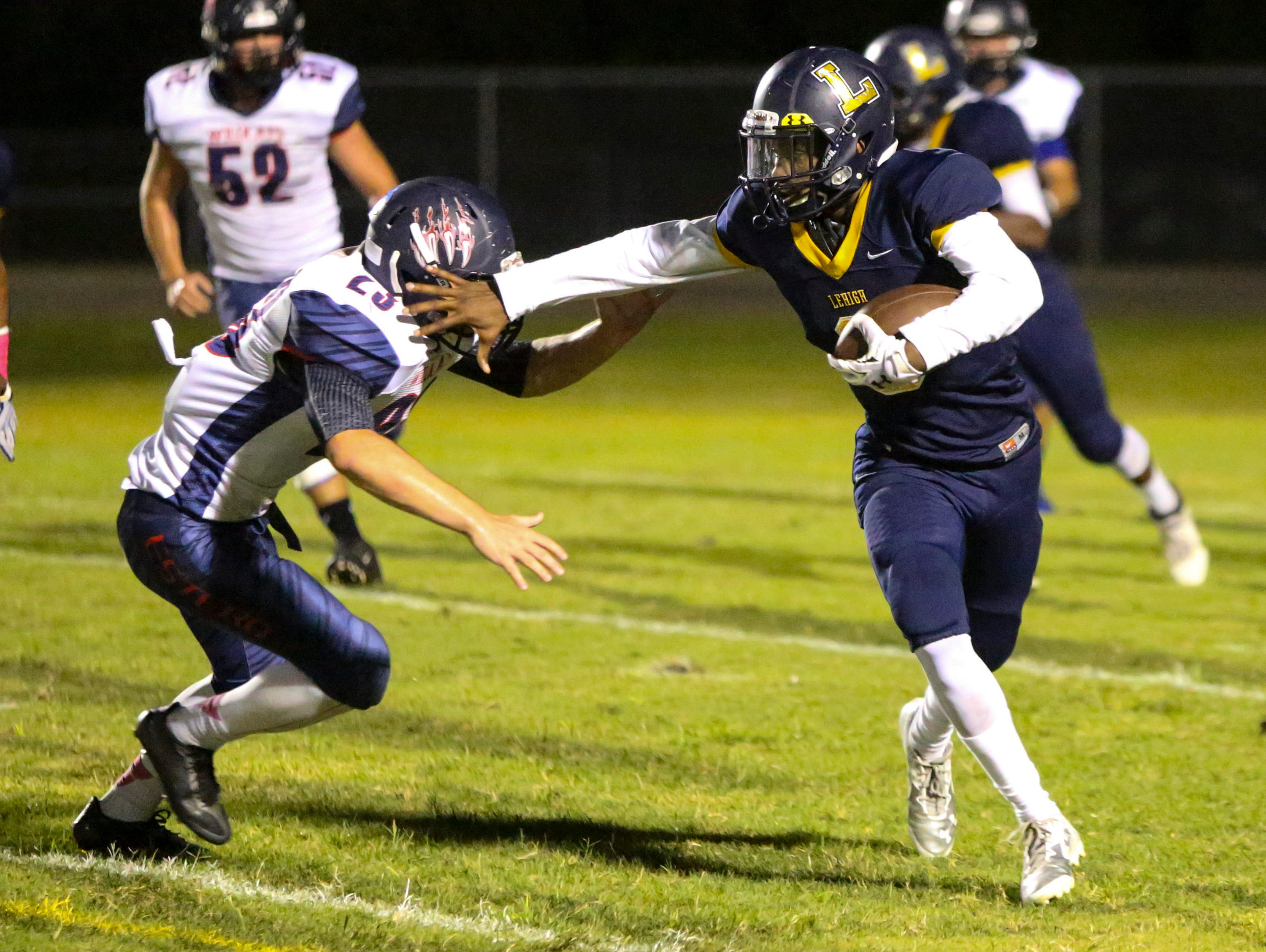 Lehigh's Delshawn Green stiff arms Estero's Jon Raus as he looks to stop Green's run. Estero went on to win 21-7.