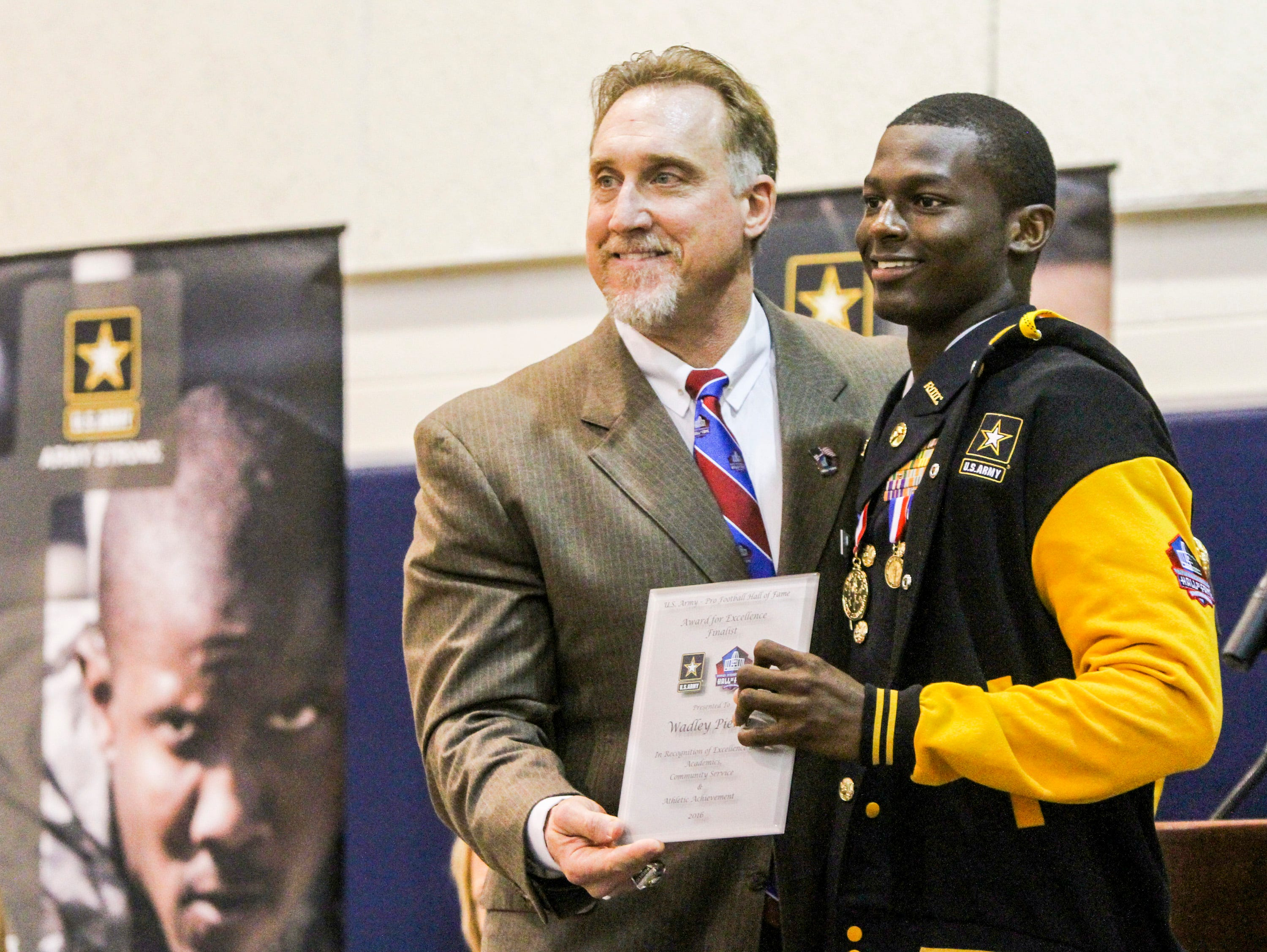 Hall of Fame NFL player Kevin Greene presents Wadley Pierre with his recognition award. Lehigh Senior High senior Wadley Pierre was nominated as a finalist for the US Army and Pro Football Hall of Fame as a student-athlete finalist for an award of excellence. Hall of Fame NFL player Kevin Greene was there to present the recognition.