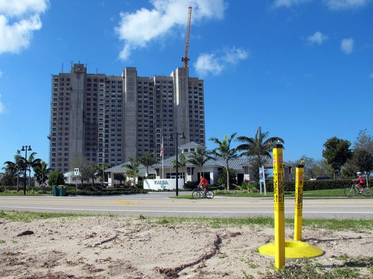 New underground natural gas lines, designated by yellow markers at right, were installed to serve the future Kalea Bay high-rise condominiums, background, on Vanderbilt Drive north of Wiggins Pass Road in North Naples.