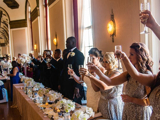 Glasses are raised for a toast at the reception of the new couple, Mr. and Mrs. Mercado July 8, 2017.