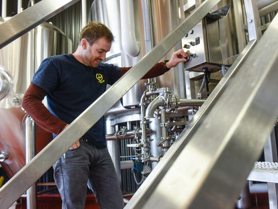 Head brewer Kevin Clark keeps an eye on equipment while