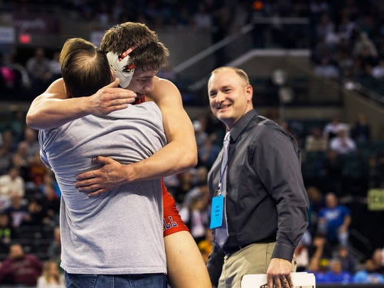 Wall's Rob Kanniard hugs one of Wall's assistant coaches while Wall head coach Brian Fischer look s on after he advanced to the 160-pound state final.