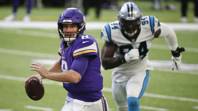 Minnesota Vikings quarterback Kirk Cousins looks to pass ahead of Carolina Panthers defensive end Efe Obada (94) during the second half of an NFL football game, Sunday, Nov. 29, 2020, in Minneapolis.