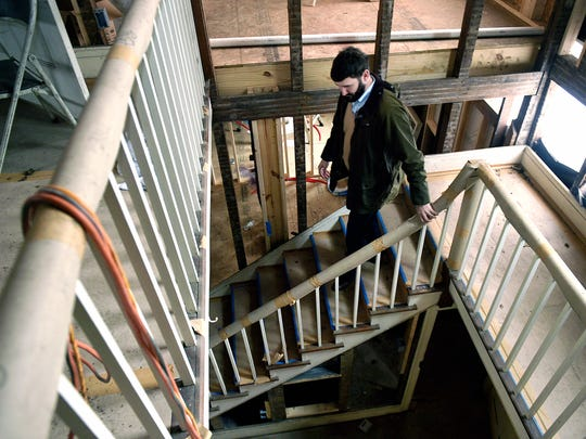"Clay Perry walks down the main staircase inside the 1850 home he and his wife purchased and are renovating. The home, which they call Boxmere, had to be gutted because it had almost fallen into disrepair. ""I have learned in historic preservation, it's a never-ending process,"" Perry said."