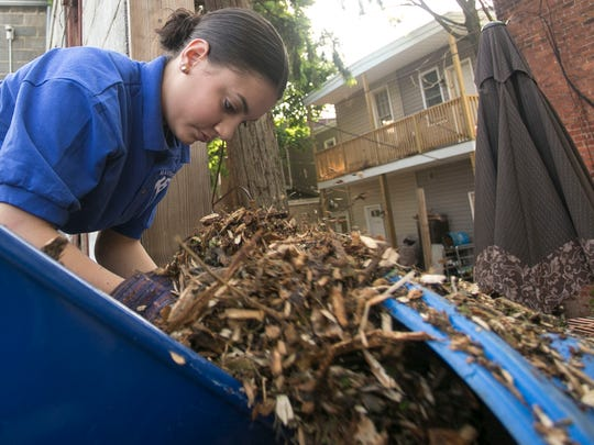 Crispus Attucks Youthbuild Charter student Angeles Rivera, 14, pushes  mulch down a shute for the courtyard section of the Royal Square Community Garden Wednesday, May 25, 2016. The Crispus Attucks HYPE Program will be volunteering for the next two weeks to continue beautifying Royal Square Garden, which is located behind DiDi and Smiling Johns at 119 South Duke Street, just off the South Howard Avenue alleyway. Amanda J. Cain photo