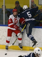 Penfield's Connor Stuewe (11) absorbs a check by Pittsford's John Avery (5).