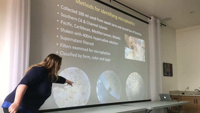 Marine ecologist and CSU Channel Islands professor Clare Steele points to tiny pieces of plastic found in sand samples from beaches in Southern California during a lecture at the Ojai Library on Saturday.