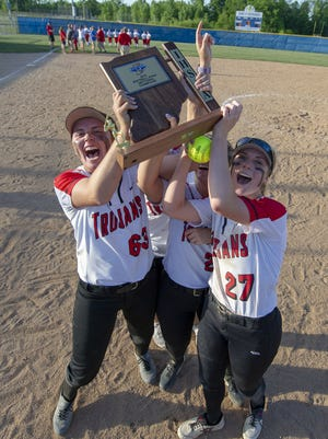 Center Grove players celebrate with their trophy after winning the championship game of an IHSAA Softball Sectional at Franklin Central High School, Wednesday, May 23, 2018. Center Grove defeated Martinsville High School 3-1.