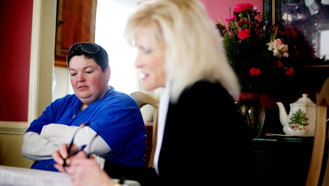 Mary Bailey fills out forms with Nancy Insco about her time she served in jail as part of a program that helps women transition back into society when they are released.