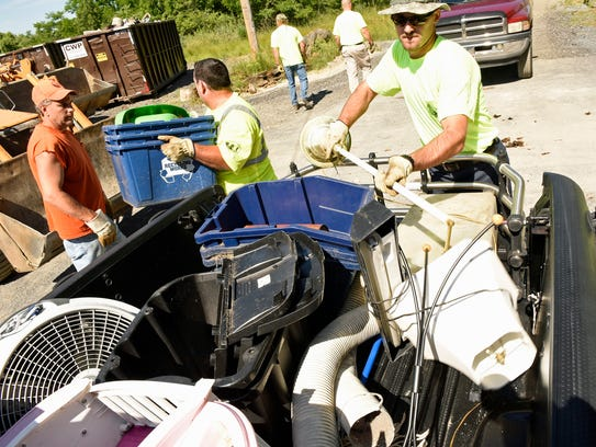 Borough employees lift items out of a pickup truck