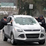 Vicksburg police traffic investigator Leonce Young, right, helps Clifton and Kim Lee push their car up a hill on East Avenue in Vicksburg on Tuesday.