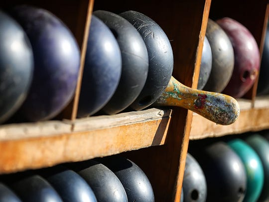 A stray bowling pin is wedged into a rack of bowling balls set aside during demolition of the Imperial Lanes on Summer Avenue which is being cleared away to make room for a Planet Fitness.