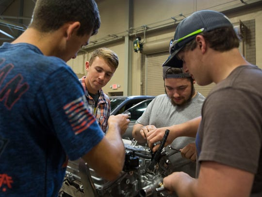 From left, Jonathan Boberg, 17, Kyle Putnan, 18, Kristian Young, 17, and Triston Stinnett, 17, work on taking apart a Toyota engine that was donated from Toyota Motor Manufacturing to Southern Indiana Career & Technical Center's Automotive Technology program on Tuesday afternoon.