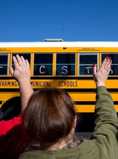 """From left, Josh Chavez, Aubrie Mamgum and Desiree Chavez wave at a bus in the funeral procession for Francisco """"Paco"""" Fernandez, Friday, Dec. 15, 2017 on Piñon Hills Boulevard in Farmington, New Mexico."""
