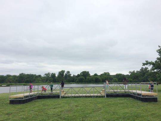 """Children play on top of the """"Wading Bridge,"""" an interactive art project that will soon be installed in the Raccoon River."""