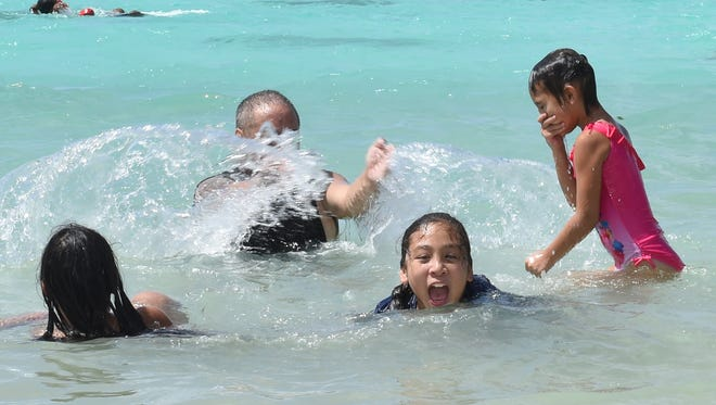 Members of the Damian family of Tamuning splash around in the waters of Ypao Beach in Tumon on July 4.