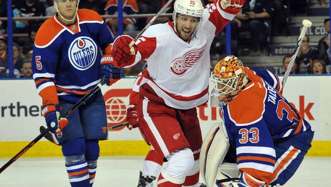 Oilers defenseman Mark Fayne (5) looks on as Red Wings center Riley Sheahan (15) skates in front of Oilers goalie Anders Nilsson (39) during the first period at Rexall Place Wednesday.