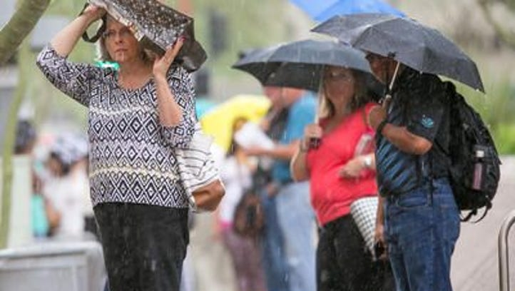 Commuters are pelted by rain in downtown Phoenix on