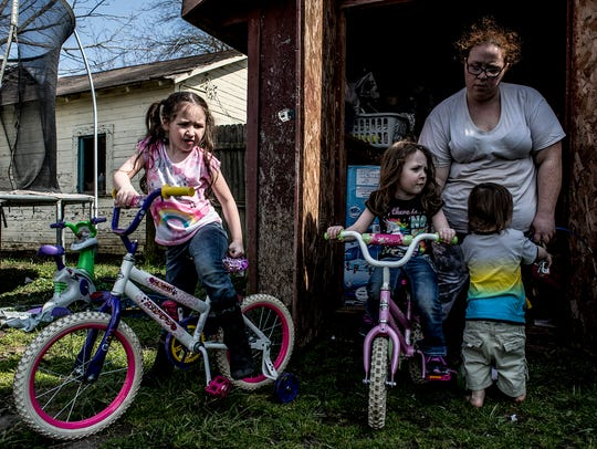 Melisa Crawford helps her children unpack their bicycles