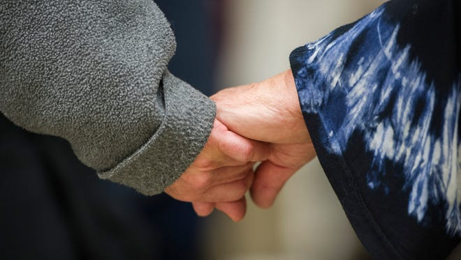"""People hold hands in prayer during """"Bridges, Not Walls,"""" an interfaith prayer service held at C.K. Newsome Community Center in Evansville, Thursday, Nov. 10, 2016. Bridge, an interfaith group in Evansville sponsored the event in order to bring various communities together in faith."""