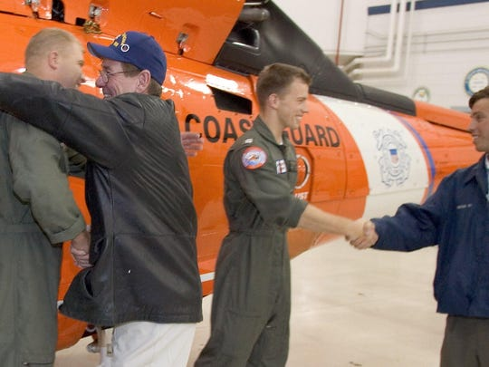 102506-Atlantic City, NJ-Rescue reunion-Coast Guard Air Station Atlantic City holds a reunion for a helicopter crew and the men they rescued off the coast of Delaware September 25. The seven men were adrift for two days in a four man liferaft   October 25, 2006.  Rescuers Tye Conklin, rescue swimmer (left) and Brian Potter, Pilot greet two of the seven men they rescued from The Chief  Master Frank Redmiles (left) and Francis Gessler.
