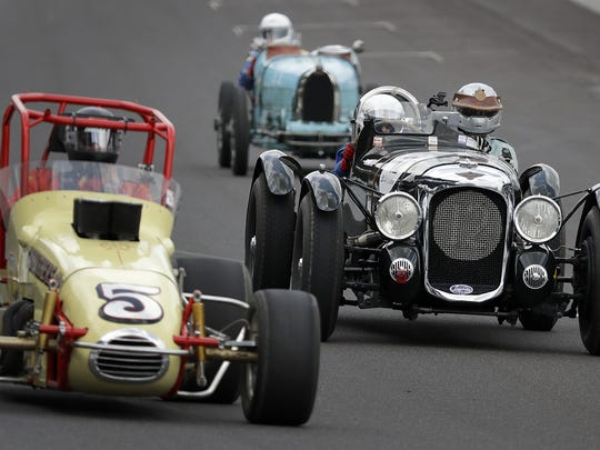Richard Morrison,right,  takes his 1939 Lagonda V12 LeMans rep into traffic as he drives around the oval at the SVRA Brickyard Vintage Racing Invitational Sunday, June 19, 2016, at the Indianapolis Motor Speedway.