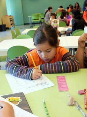Stephanie Duran keeps her bookmark close at the César Chávez Library's after-school homework program.