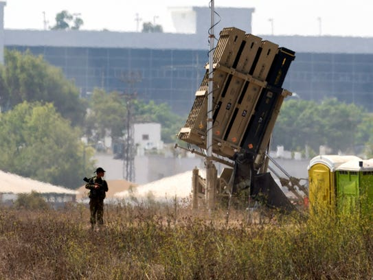 An Israeli soldier guards an Iron Dome missile defense