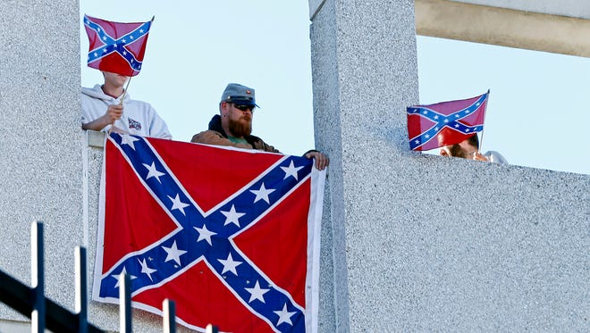 Michael Adams Jr., Tim Arnold and Dustin Smith fly the Confederate Flag outside to Bon Secours Wellness Arena before second round of the 2017 NCAA tournament game between Arkansas and North Carolina.