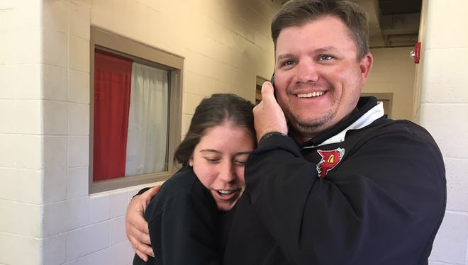 Parkway coach Neil May receives a hug from softball  manager Olivia Cheatham while talking on the phone with Panther boys basketball coach Mike Guess Tuesday afternoon.