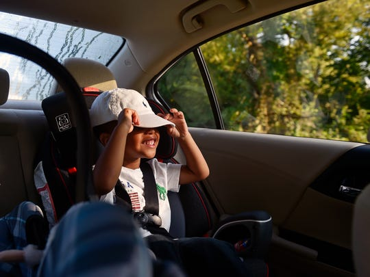 Kenyetta Redman's 3-year-old son pulls his cap visor over his eyes on his way to school on Wednesday, Aug. 30, 2017.