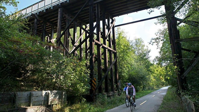 A pair of cyclists ride the Glacial Drumlin State Trail under a bridge just east of the Wales trailhead and parking lot.