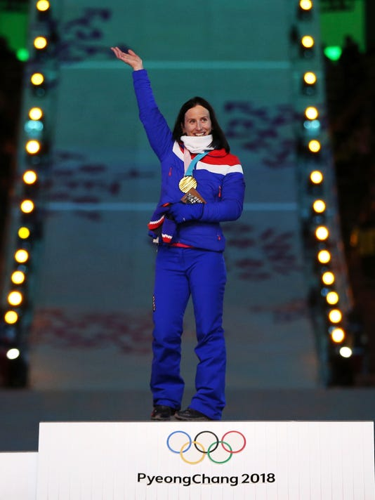 Norway's Marit Bjoergen, gold, waves during the medals ceremony for the women's 30k cross-country skiing at the closing ceremony of the 2018 Winter Olympics in Pyeongchang, South Korea, Sunday, Feb. 25, 2018. (AP Photo/Natacha Pisarenko)