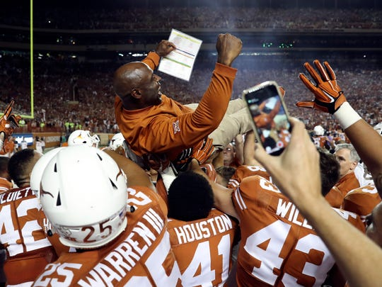 Texas Longhorns players lift up head coach Charlie