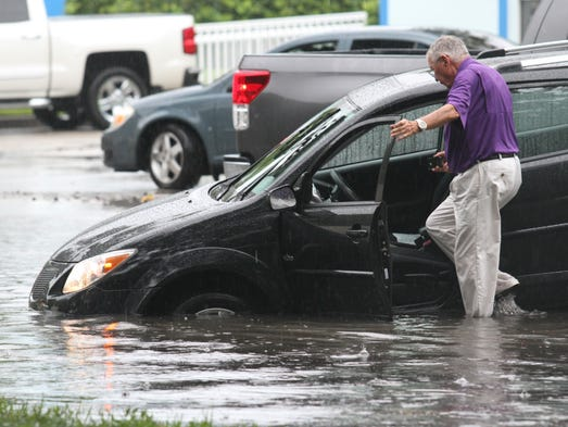 Darrell March, of Naples, gets back into his car as he prepares it to be towed out of the water near the intersection of Airport Pulling Road and Radio Road in Naples on Monday.